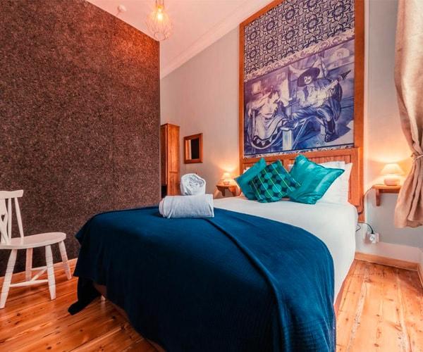 Quarto com frisos aplicados a emoldurar painel de azulejos e parede de separação do wc em cortiça
