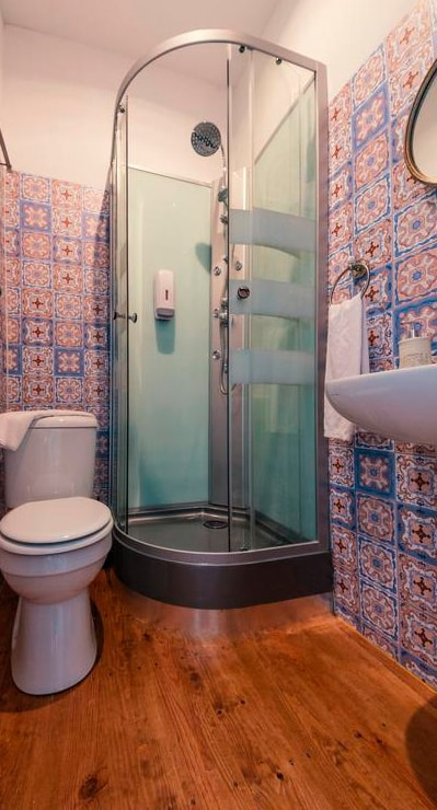 Casa de banho instalada no interior do quarto, com painéis Dibond a simular azulejo